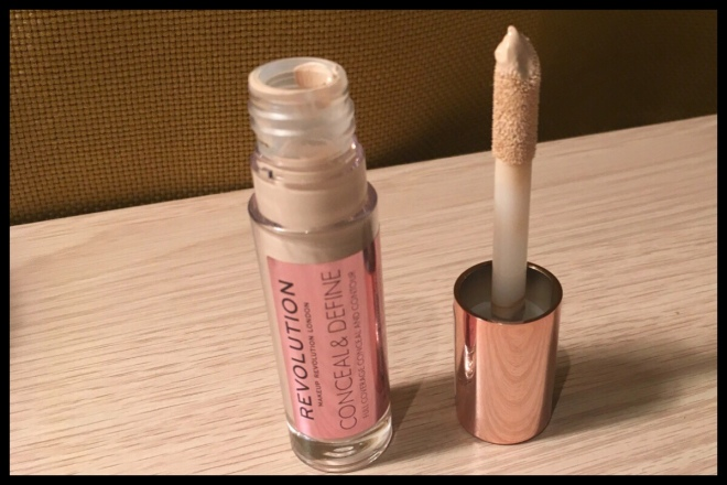 The Makeup Revolution Conceal and Define Concealer open with the lid next to it showing the product and applicator