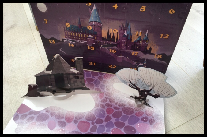 Inside the Funko Pop Advent Calendar with the Hogwarts scene printed on the doors. There is a pop up Whomping Willow and Hagrid's Hut in front on a snowy base.
