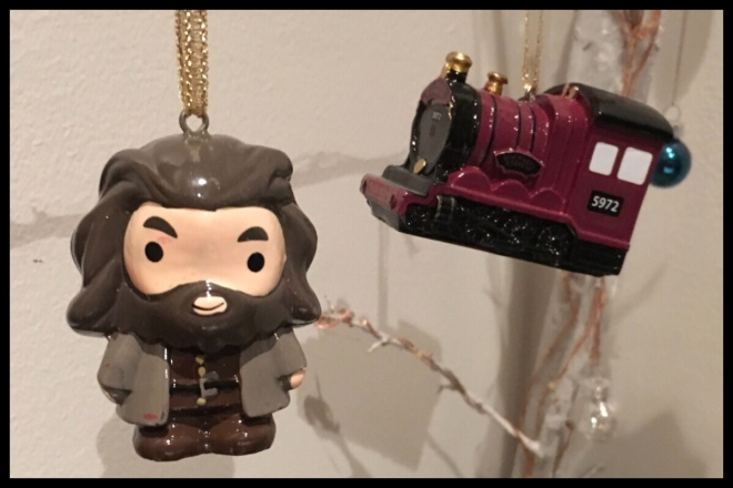Two Harry Potter Christmas decorations hanging in front of a white wall, one of Hagrid's and one of the Hogwarts Express