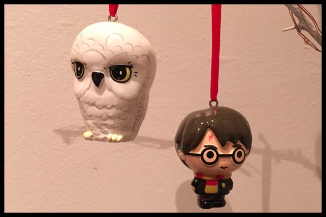Two Harry Potter Christmas decorations hanging in front of a white wall, one is Harry Potter and another is Hedwig the snowy owl