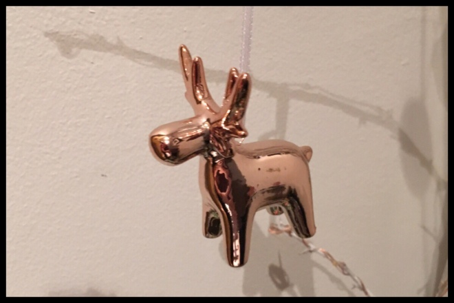 A rose gold moose Christmas decoration hanging in front of a white wall