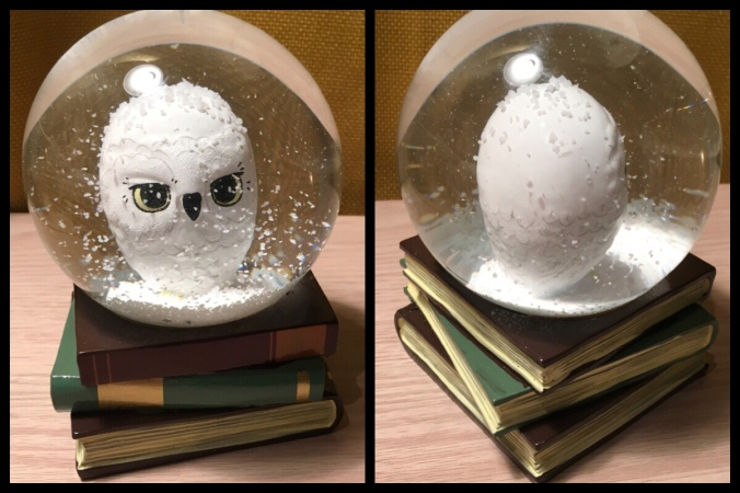 Two pictures showing the front and back of the Hedwig snow globe. It has Hedwig sat in the globe with white snow and stars floating around. The globe is sat on a pile of books.