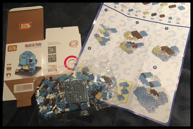 The inside of the Squirtle bag with the small bag of pieces, flat pack box and instructions unfolded.