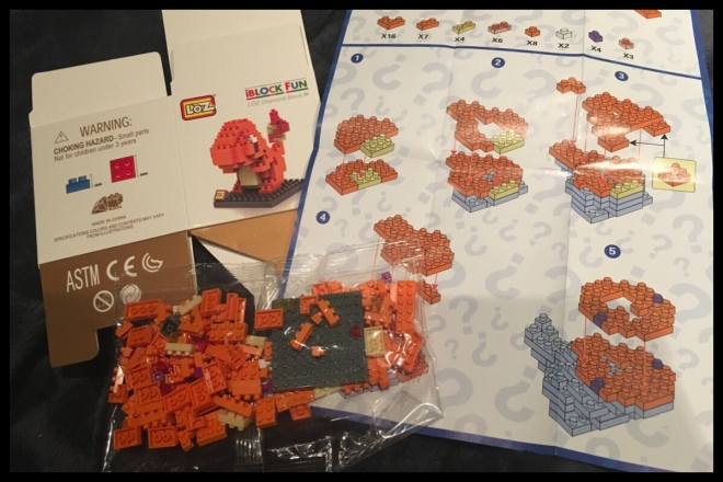 The inside of the Charmander bag: the bag of pieces for the model, the unfolded instructions and the flat pack box