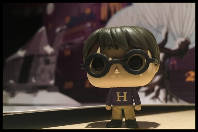 An image showing the Harry Potter Funko Pop figure. He has the Christmas jumper with an H knitted on it he got from Mrs Weasley
