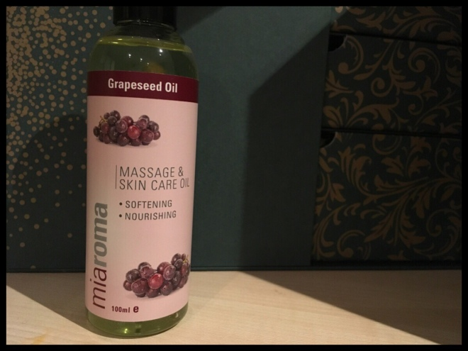The front of the Miaroma Grapeseed Oil bottle in front of the Holland and Barrett advent calendar