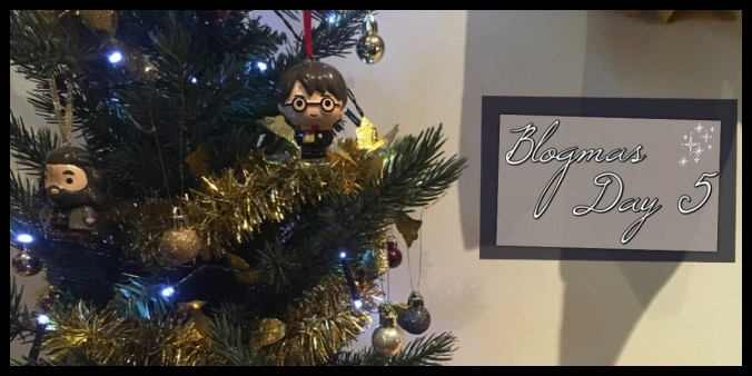 An image of an artificial Christmas tree with gold and maroon baubles on and some Harry Potter Decorations.