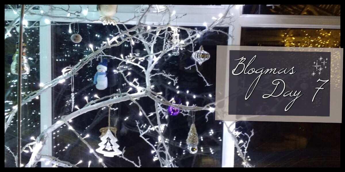 A white tree covered in lights and decorations with Blogmas Day 7 in front