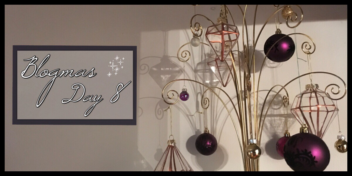 An image of a golden wire Christmas tree decoration with gold, rose gold and dark purple baubles hanging from it. To the left is the title Blogmas Day 8