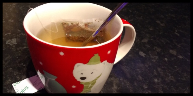A Christmas mug with a polar bear on it, inside is green tea and the teabag string is hanging over the edge