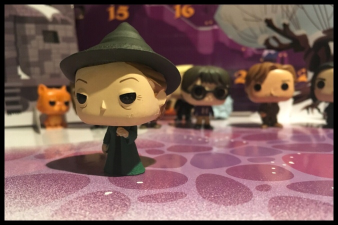 The Professor McGonagall figure is stood on the fold out base of the advent calendar with previous Funko Pop figures in the background
