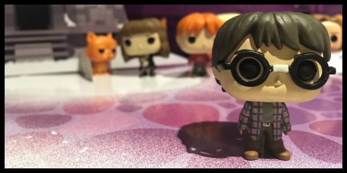 The figure is Harry Potter in a check shirt and jeans and with his glasses broken and fixed with tape in the middle