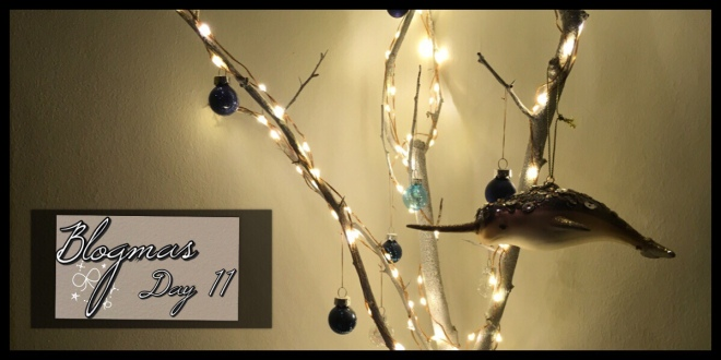 An image of a lit up white branch with baubles hanging from it, on the right is a narwhal decoration hanging off the branch