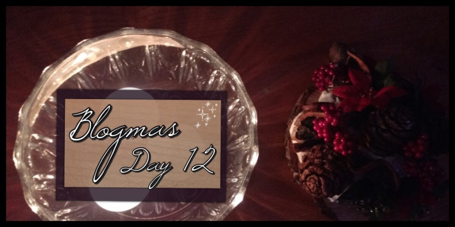 The Blogmas Day 12 header image. It has candles on the left lighting up a decoration with berries, cones and dried oranges on the right