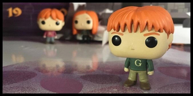 The George Weasley figure is stood to the right in focus, with Ron and Ginny in the background