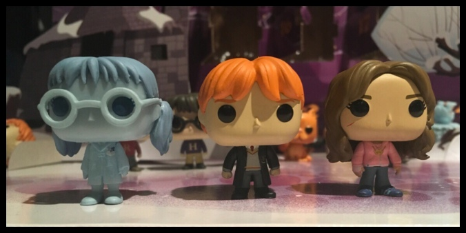 The three Harry Potter Funko Pop figures, left to right: Moaning Myrtle, Ron in school uniform and Hermione in the pink hoodie and jeans outfit from the Prisoner of Azkaban movie.