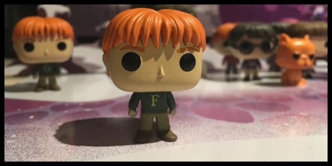 The Fred Funko Pop figure is in the foreground. He is wearing a green jumper with the letter F on it.