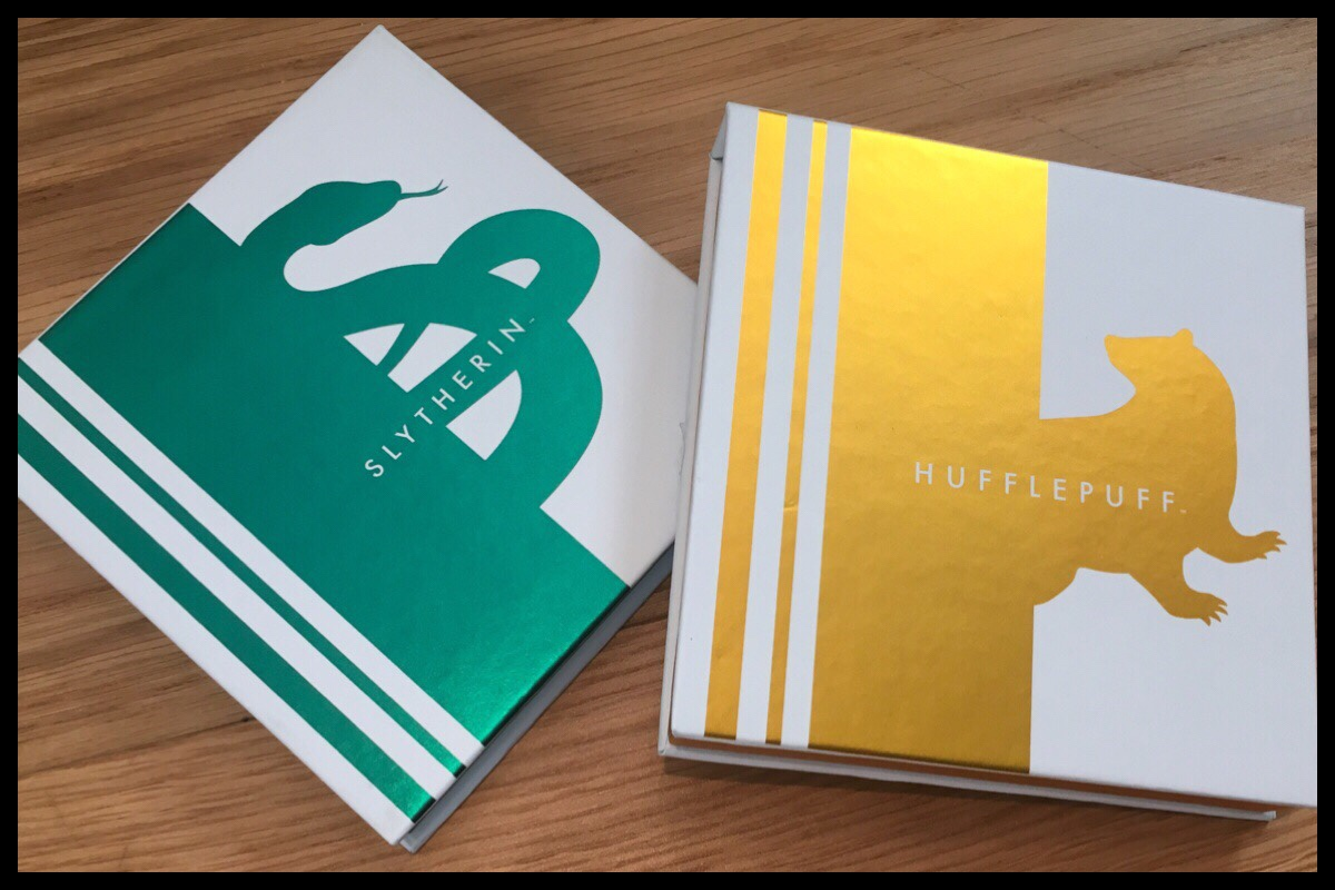 The closed eyeshadow palettes, showing the house artwork on the front. Slytherin has a metallic green snake and Hufflepuff a metallic gold badger
