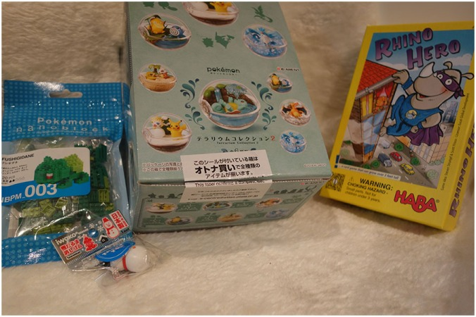 From left to right: the bag for the Bulbasaur nanoblocks, a small free snowman eraser, the box with six Pokemon Terrarium sets in it and the Rhino Hero board game