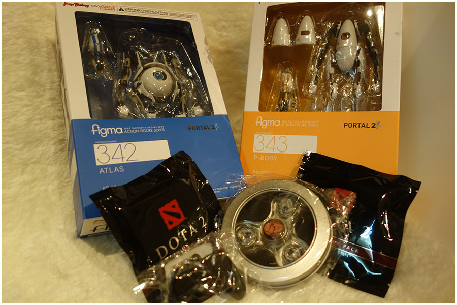 The two Figma figures, P-Body and Atlas, from Portal 2 and in front are some free products including a Dota fidget spinner, two blind bags and an XBox controller keyring