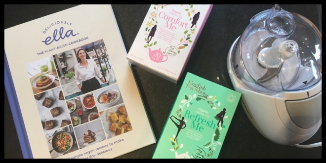 On a table are the Deliciously Ella cookbook, two packs of tea from the English Tea Shop and the Kenwood mini chopper