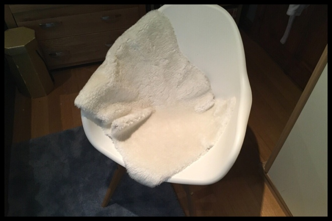 On the floor is a blue rug and on top of it is stood a white chair with a white fake sheep skin rug thrown over the back.