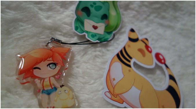 A photo of the extra things that came in the order. There are two stickers and an acrylic Misty charm