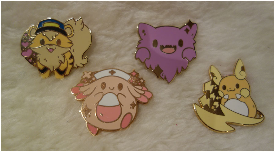 The four enamel pins. Left to right: a growlithe with a hat dressed as a police officer, Chansey wearing a nurse's hat, a cute fluffy looking Haunter and an Alolan Raichu with lightning bolts