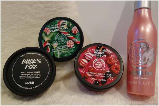 Three empty pots and a spray bottle. In the pots were Lush's Buck's Fizz Body Conditioner and two mini versions of the Body Shop Body Butter in Peppermint Candy Cane and Berry Bon Bon. The spray bottle had Soap and Glory Original Pink Body Spray in it.