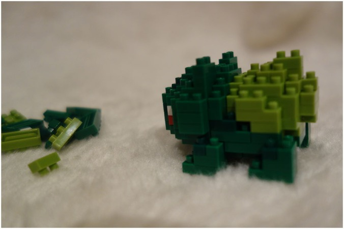 A side view of the Bulbasaur model assembled with some of the spare Nanoblocks next to it