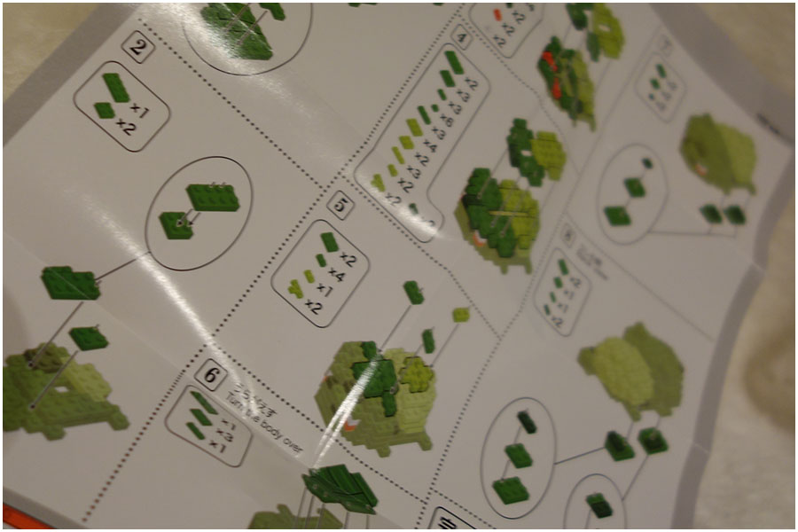 A photo of the sheet of instructions showing some of the steps to build the Bulbasaur Nanoblocks model