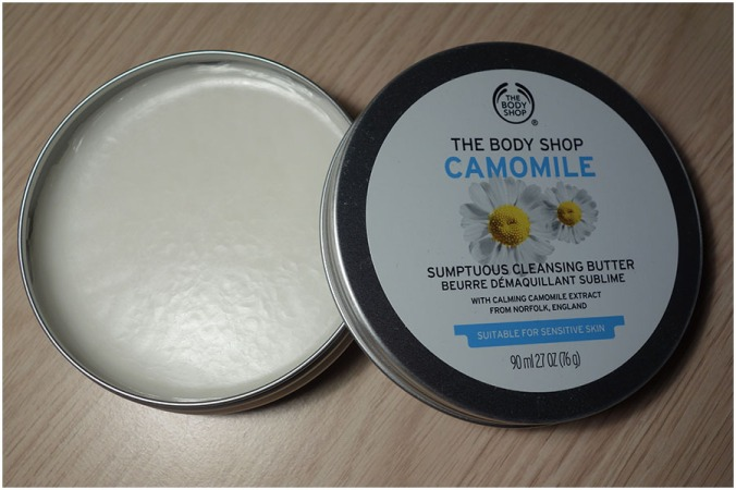 The Camomile Sumptuous Cleansing Butter tin open. On the left is the base of the tin with the product untouched and on the right is the lid with the top design showing