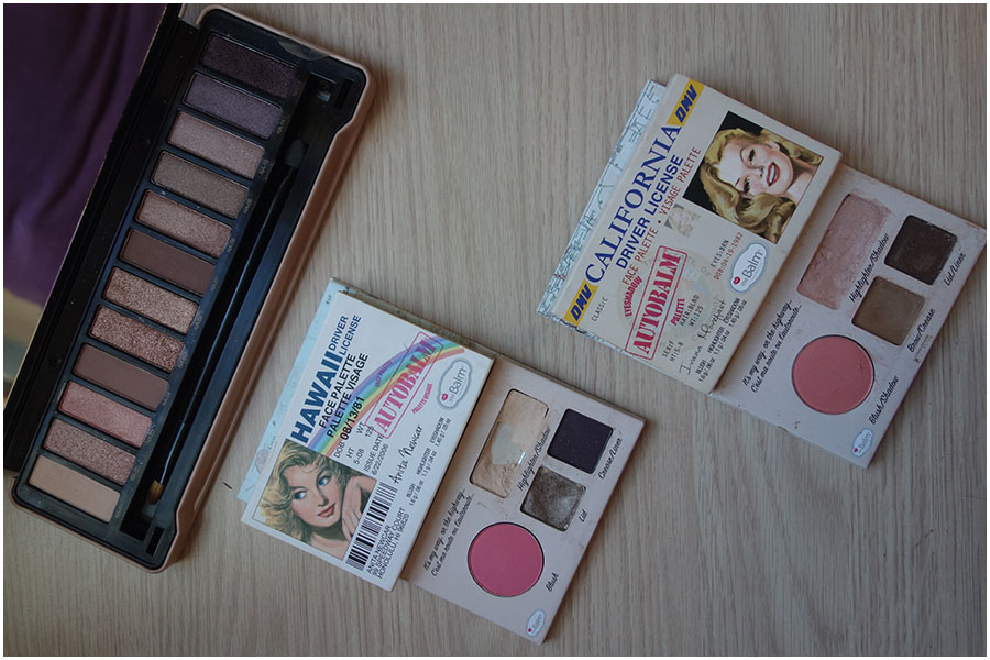 three palettes open on a table. Left to right: the IDC Color natural eyes palette, The Balm Hawaii Autobalm palette and the California Autobalm palette.