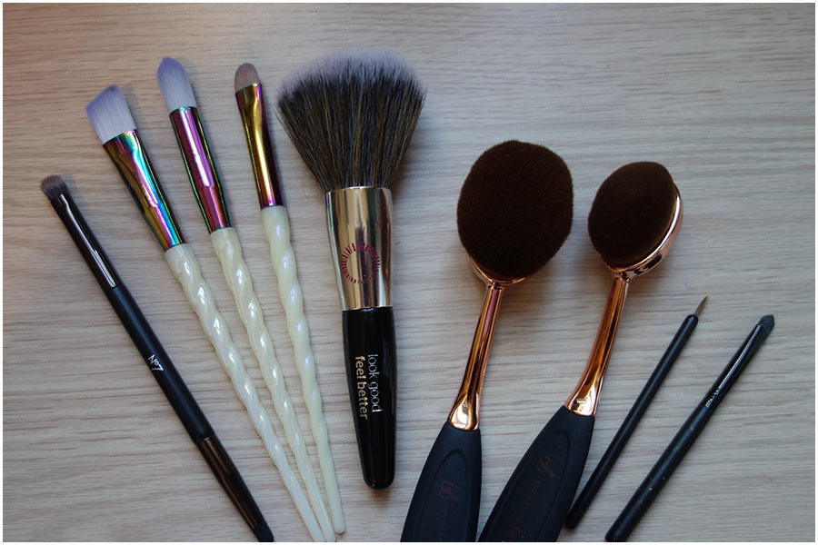 Eight brushes laid out on the desk.
