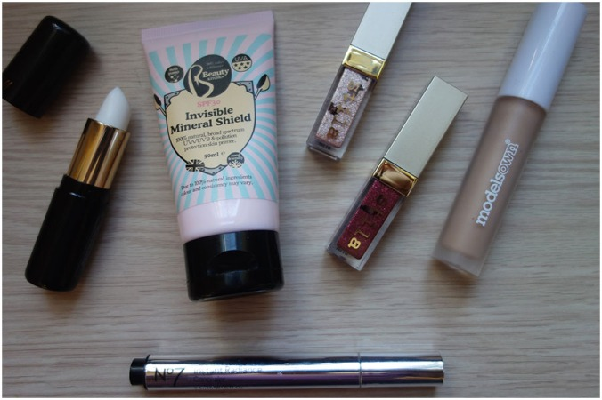 A mix of makeup products on the desk. Left to right: H&M lip primer, Beauty Kitchen Invisible Mineral SHield, two Stila Glitter and Glow, Models Own Matte eyeshadow primer. Underneath is the No7 illuminating under eye concealer