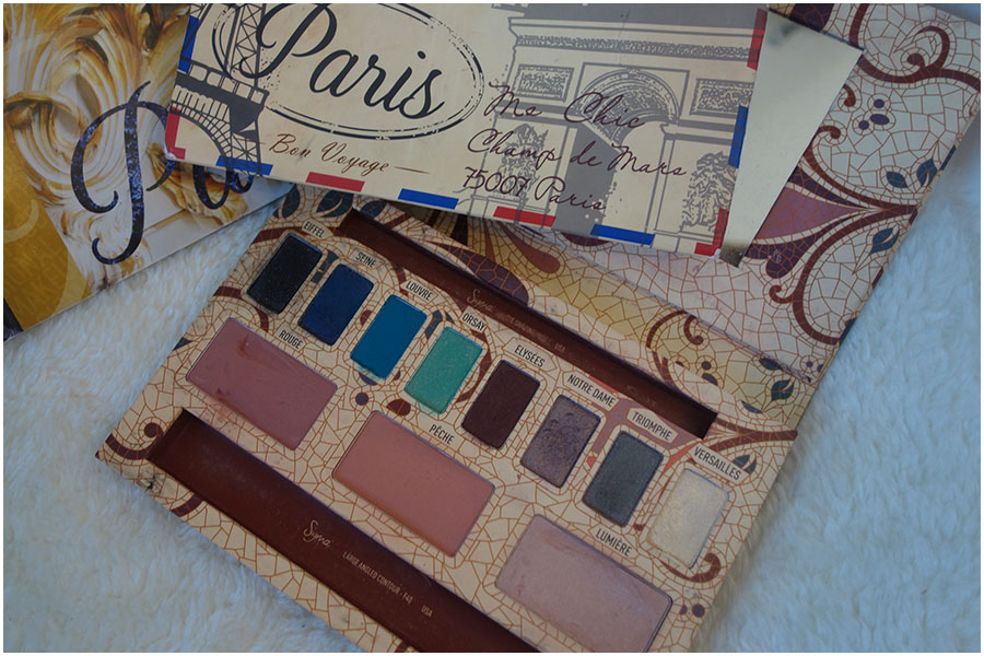 The Stila Limited Edition Paris palette open on a chair with eight eyeshadows, two blushes and a highlighter