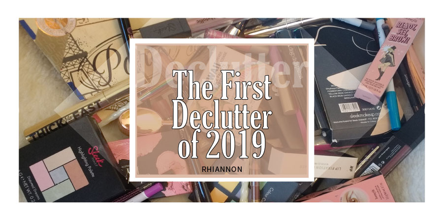 The First Declutter of 2019 title image. Behind the text is a photo of all the products I decluttered spread out on a chair