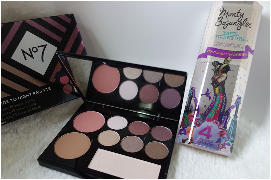 The two free gifts with purchase. On the left is the open No7 Nude to Night Palette with six eyeshadows, a blush, a bronzer and a highlight. On the right is a small box of chocolates from Monty Bojangles