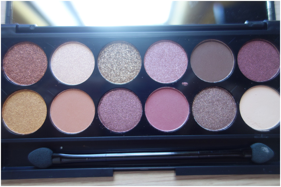 The open palette, the twelve eyeshadows with eight shimmers and four mattes. At the bottom of the palette is the sponge applicator.