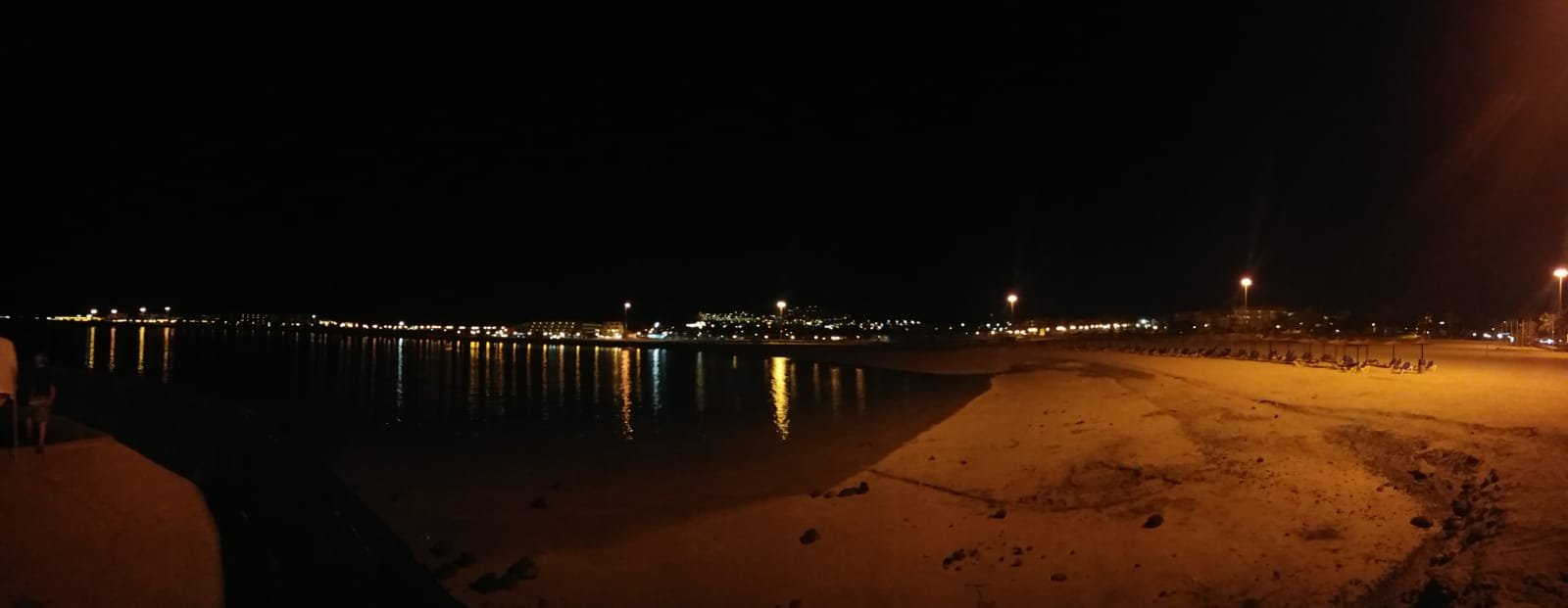 A night view over the beach from the entrance to the resort. You can see the beach that's well light, the dark water and the reflection of lights from other hotels around the other side of the bay.