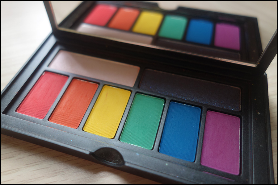 A photo of the palette open with the mirror showing a reflection of the eyeshadows. At the top of the palette are two large duochrome shades with six bright colours in rainbow colours from red to purple