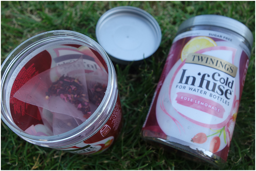 On the left is a the watermelon, strawberry and mint tub open and showing the tea bags inside, the rose and lemonade tub is lying on its side showing the front of the label next to it.