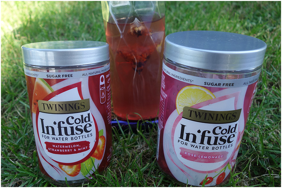A photo of the two tubs standing on the grass with the bottle of the infused drink behind them