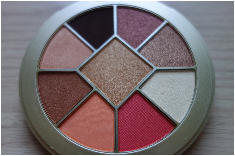 A flat image of the eyeshadows in the palette. It's all browns and golds except for a bright orange, a red and an off white