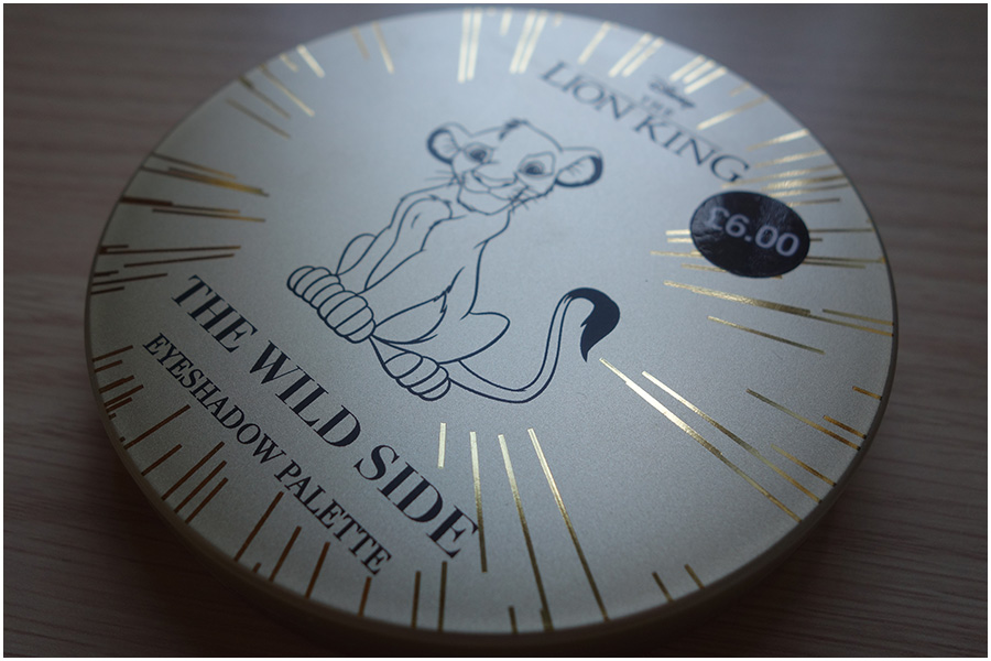 The palette lid closed. It has a satin antique gold colour background with lines like rays from the centre in shiny gold. There's a line drawing of the original Disney Simba cartoon in the middle