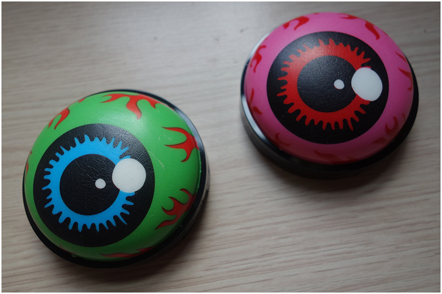 The outside of the packaging. On the left is a green cartoon eyeball with a blue iris, the packaging for Terrif-Eye. The right shows a bright pink eyeball with a red iris that's the compact for Eye See You