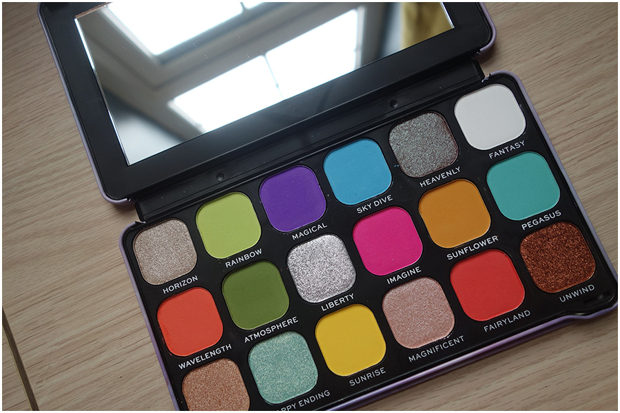 The palette is open on the desk with the lid flat on the surface. It shows all eighteen of the eyeshadow shades.
