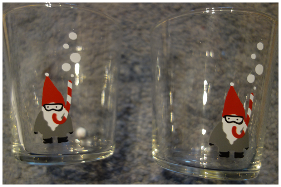 Two glasses laying on a blue carpet. There's a gnome using a candy cane as a snorkel with bubbles going u to the top of the glass