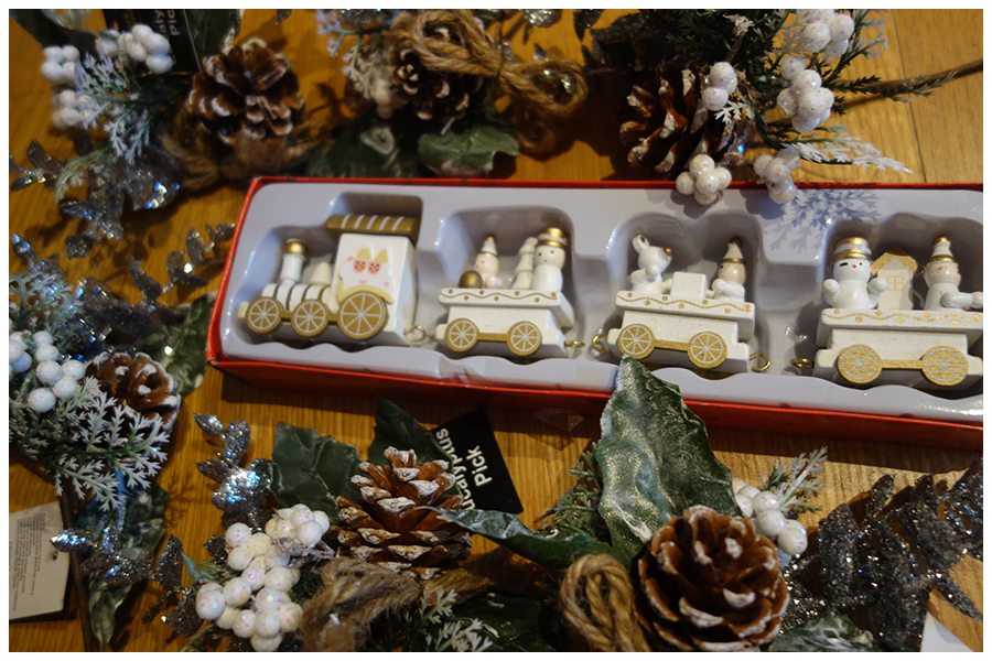 in the middle of the photo is a wooden train in white with gold details and three carriages with Christmas characters in. Around it are six 'picks' or smack bunches of fake leaves and berries with a cone and fake snow on them