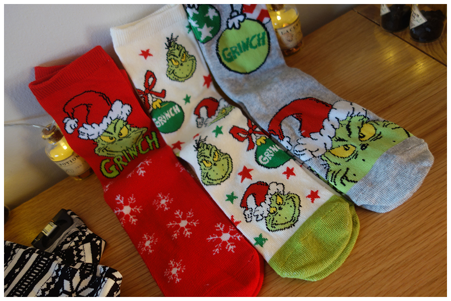 the three pairs of Grinch socks, one is red with snowflakes, the middle is cream with the Grinch heads and baubles and the right pair is grey with a Grinch face and the bauble at the top
